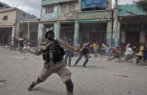 A national police officer throws a tear gas grenade during riots in Port-au-Prince, Sunday, Jan. 17, 2010.