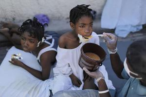 An injured girl is feed by a hospital volunteer at the general hospital in Port-au-Prince, Saturday, Jan. 16, 2010.