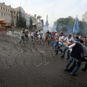 Lebanese protesters pull a barbed-wire barrier during clashes after the funeral of Brigidier General Wissam al-Hassan (AP)