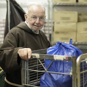 Capuchin monk Brother Kevin Crowley helps volunteers hand out nearly 900 food parcels to Dublin's poorest
