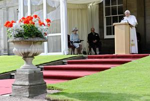 Queen Elizabeth II and the Duke of Edinburgh listen as Pope Benedict XVI addresses a crowd in the gardens at the Palace of Holyroodhouse in Edinburgh, on the first day of his four day visit to the United Kingdom
