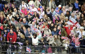 LONDON, ENGLAND - APRIL 29:  Royal supporters wave British Union Jack flags along the processional route on the day of the wedding of Britain's Prince William and Catherine Middleton, on April 29, 2011, in London, England.  The marriage of Prince William, the second in line to the British throne, to Catherine Middleton is being held in London today. The Archbishop of Canterbury conducted the service which was attended by 1900 guests, including foreign Royal family members and heads of state. Thousands of well-wishers from around the world have also flocked to London to witness the spectacle and pageantry of the Royal Wedding and street parties are being held throughout the UK. (Photo by Damien Meyer - WPA Pool/Getty Images)