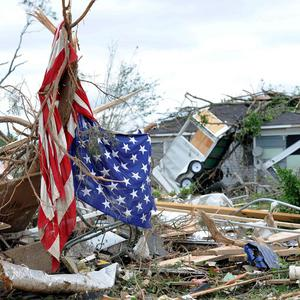 An American flag hangs over the rubble from the tornado that struck Concord, Alabama (AP)