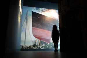 BELFAST, NORTHERN IRELAND - MARCH 27:  A girl looks up at a painting depicting the launch of The Titanic at the Titanic Belfast visitor attraction on March 27, 2012 in Belfast, Northern Ireland. The Titanic Belfast Experience is a new £90 million visitor attraction opening on March 31, 2012. One hundred years ago the maiden voyage of the ill-fated passenger liner Titanic sank after hitting an iceberg in the Atlantic on the night of April 14, 1911 with the loss of 1517 lives.  (Photo by Peter Macdiarmid/Getty Images)