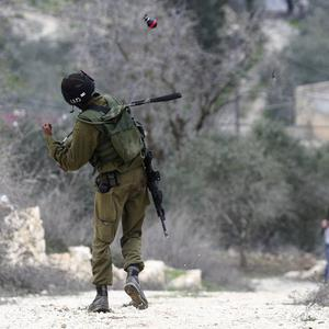 An Israeli soldier throws a tear gas grenade during clashes between Jewish settlers and Palestinians in the West Bank (AP/Nasser Ishtayeh)
