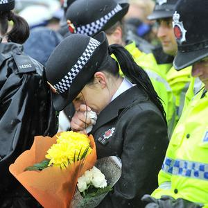 A police officer bows her head during a vigil for Pcs Fiona Bone, 32, and Nicola Hughes, 23
