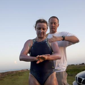 Penny Palfrey and her husband Chris rub cream on her body in preparation for her bid to complete a record swim from Cuba to Florida (AP)