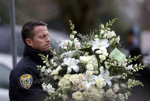 A police officer carries flowers into a funeral service for 6-year-old Noah Pozner, Monday, Dec. 17, 2012, in Fairfield, Conn. Pozner was killed when a gunman walked into Sandy Hook Elementary School in Newtown Friday and opened fire, killing 26 people, including 20 children. (AP Photo/Jason DeCrow)