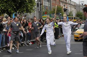 John and Edward (Jedward) Grimes carry the Olympic Flame past the GPO on O'Connell St in Dublin city centre on Day 19 of the Olympic Torch relay
