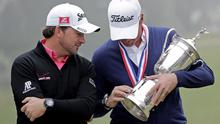 Webb Simpson shows the championship trophy to Graeme McDowell, of Northern Ireland, after the U.S. Open Championship golf tournament Sunday, June 17, 2012, at The Olympic Club in San Francisco. (AP Photo/Eric Gay)