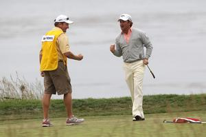 Graeme McDowell of Northern Ireland celebrates with his caddie Ken Comboy after making par on the 18th hole to win the 110th U.S. Open at Pebble Beach Golf Links on June 20, 2010 in Pebble Beach, California