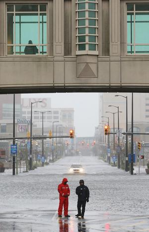 ATLANTIC CITY, NJ - OCTOBER 29:  People stand in a flooded street as Hurricane Sandy movs off the east coast on October 29, 2012 in Atlantic City, New Jersey. Governor Chris ChristieÄôs emergency declaration is shutting down the cityÄôs casinos and 30,000 residents were ordered to evacuate.  (Photo by Mario Tama/Getty Images) *** BESTPIX ***