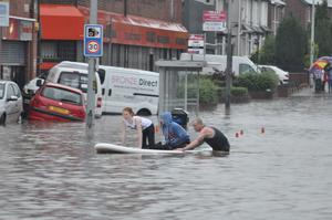 East Belfast surfboard superhero rescues flood victims. Image submitted by Conor Dunn  June 2012