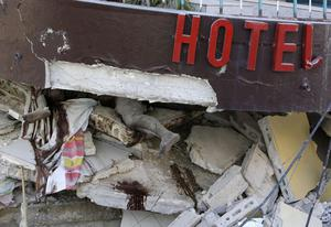 A body is buried in the rubble of a hotel in the aftermath of an earthquake in Port-au-Prince, Haiti  Friday, Jan. 15, 2010