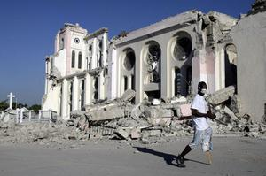 A man, wearing a face mask as a precaution against infections, walks past the collapsed Cathedral of Port-au-Prince, Friday, Jan. 15, 2010.