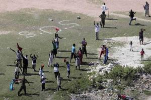 People wave towards a helicopter in Port-au-Prince, Friday, Jan. 15, 2010. A powerful earthquake struck Haiti Tuesday