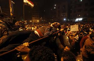 Protesters carry a man wounded during clashes with Egyptian riot police in Tahrir Square in Cairo, Egypt, Monday, Nov. 21, 2011. Egypt's army-appointed government handed in its resignation Monday, trying to stem a spiraling crisis as thousands of protesters in Cairo's Tahrir Square clashed for the third straight day with security forces in violence that has killed dozens of people and posed the most sustained challenge yet to the rule of the military. (AP Photo/Khalil Hamra)