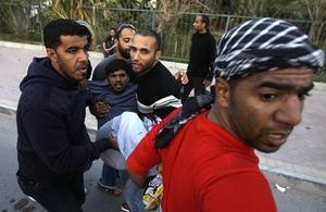 An unidentified Bahraini anti-government protestor is carried to a vehicle to be taken to a hospital after being wounded during a demonstration in Manama, Bahrain, Friday, Feb. 18, 2011. Soldiers fired tear gas and shot heavy weapons into the air as thousands of protest marchers defied a government ban and streamed toward the landmark square that had been the symbolic center of the uprising against the Gulf nation's leaders. (AP Photo)