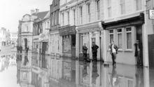 Downpatrick's Market Street, under a flood of water, mirrors the buildings.  9/5/1966