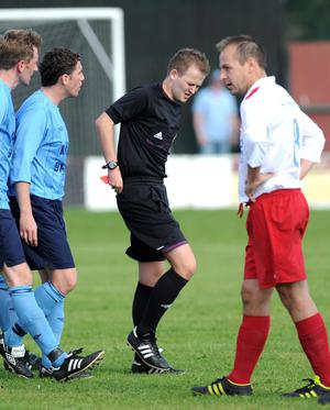 Referee Keith Kennedy grimaces in pain from an  injury to his right ankle which he incurred as he rushed to give Ards Rangers' Jamie Patterson the red card for his challenge on Ards' Kyle McDowell. The referee could not continue, leading to the match being abandoned