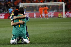 Spain goalkeeper Iker Casillas, back to camera, hugs Sergio Busquets  after the World Cup final soccer match between the Netherlands and Spain at Soccer City in Johannesburg, South Africa