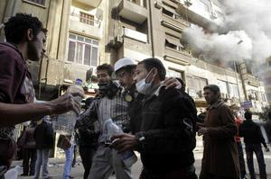 Egyptian protesters help an injured journalist, Maher Malak, from the scene of a building fire, seen in background, near Tahrir Square in Cairo, Egypt, Monday, Nov. 21, 2011.  Local people at the scene blame the fire on police firing tear gas in the area.  Egyptian riot police clashed Monday with thousands of protesters demanding that the ruling military quickly announce a date to hand over power to an elected government. (AP Photo/Amr Nabil)