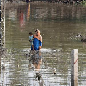 A woman carries her child through floodwater in Camp Koroona village, Pakistan
