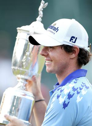 Rory McIlroy of Northern poses with the trophy after his eight-stroke victory on the 18th green during the 111th U.S. Open