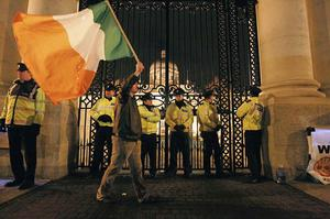 A protester waves the Irish tricolour outside Government Buildings, Dublin, after the Irish Government tonight confirmed it will seek a bailout loan from the International Monetary Fund (IMF) and Europe