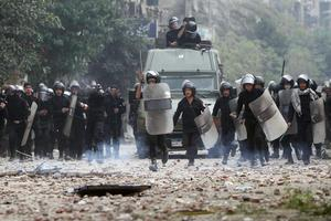 CORRECTS CREATION DATE - Egyptian riot police are seen on the move during clashes with protesters in Tahrir Square in Cairo, Egypt, Sunday, Nov. 20, 2011. Firing tear gas and rubber bullets, Egyptian riot police on Sunday clashed for a second day with thousands of rock-throwing protesters demanding that the ruling military quickly announce a date to hand over power to an elected government. The police battled an estimated 5,000 protesters in and around central Cairo's Tahrir Square, birthplace of the 18-day uprising that toppled authoritarian leader Hosni Mubarak in February. (AP Photo/Ahmed Ali)