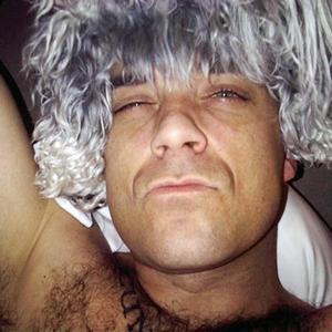 Robbie Williams poses with his dogs on his head as wigs
