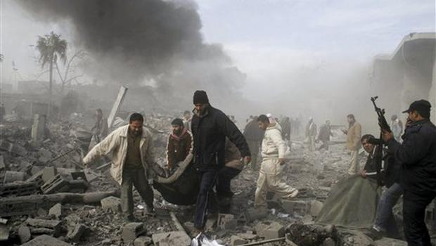Palestinians carry the body of a Palestinan from the rubble following an Israeli missile strike in Rafah, southern Gaza Strip, Saturday, Dec. 27, 2008.Israeli warplanes demolished dozens of Hamas security compounds across Gaza on Saturday in unprecedented waves of simultaneous air strikes. Gaza medics said more than 120 people were killed and more than 250 wounded.(AP Photo/Hatem Omar)