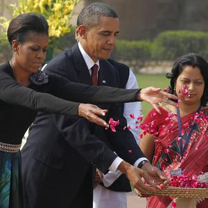 Barack Obama and wife Michelle sprinkle flowers after laying a wreath at a memorial in New Delhi (AP)