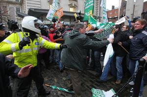 Sinn Fein protestors including TD Aengus O''Snodaigh tussle with Gardai at the gates of Government Buildings in Dublin