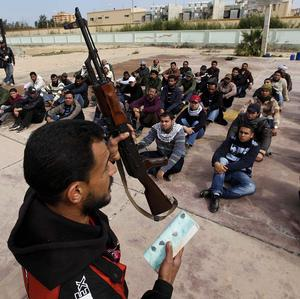 A former Libyan army soldier shows new rebel recruits how to use an assault rifle during a training session (AP)