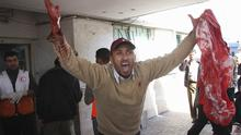 A Palestinian man reacts as he holds a blood stained sheet at the entrance to Shifa Hospital in Gaza City, Thursday, Jan. 15, 2009. Israeli forces shelled the United Nations headquarters in the Gaza Strip on Thursday, setting the compound on fire as U.N. chief Ban Ki-moon was in the area on a mission to end Israel's devastating offensive against the territory's Hamas rulers. (AP Photo/Thaer Al-Hasani)