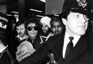 Michael Jackson is lead through a crowd by policeman on a promotionial tour of Great Britain in London in 1985