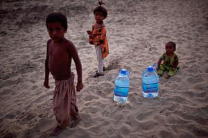 Children displaced from their homes by flooding stand near bottles of water donated by roadside motorists