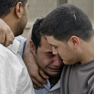 An Iraqi man is consoled by friends at the scene of the Catholic Church siege in Baghdad