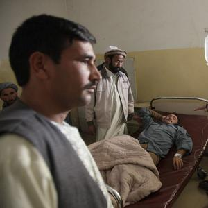 An Afghan police officer who was wounded in a suicide bombing lies in a hospital bed in Baghlan, Afghanistan (AP)