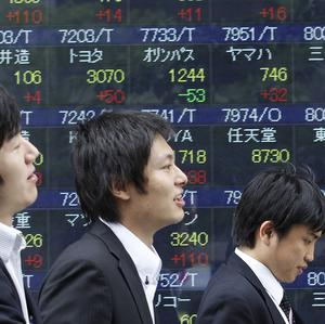 People walk by an electronic stock board of a securities firm in Tokyo, as Japan's Nikkei 225 index fell by one per cent (AP)