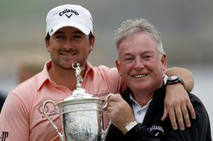 Graeme McDowell (L) of Northern Ireland celebrates with the trophy alongside his father Ken on the 18th green after winning the 110th U.S. Open at Pebble Beach Golf Links on June 20, 2010 in Pebble Beach, California