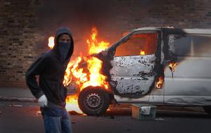 LONDON, ENGLAND - AUGUST 08:  A hooded youth walks past a burning vehicle in Hackney on August 8, 2011 in London, England. Pockets of rioting and looting continues to take place in various boroughs of London this evening, as well as in Birmingham, prompted by the initial rioting in Tottenham and then in Brixton on Sunday night. It has been announced that the Prime Minister David Cameron and his family are due to return home from their summer holiday in Tuscany, Italy to respond to the rioting. Disturbances broke out late on Saturday night in Tottenham and the surrounding area after the killing of Mark Duggan, 29 and a father-of-four, by armed police in an attempted arrest on August 4.  (Photo by Peter Macdiarmid/Getty Images)