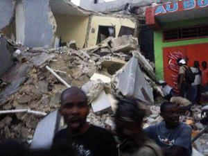 This photo provided by Carel Pedre shows people running past rubble of a damaged building in Port-au-Prince, Haiti, Tuesday, Jan. 12, 2010