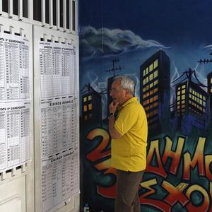 A Greek man checks the voting lists at a voting centre during the elections in Athens (AP)