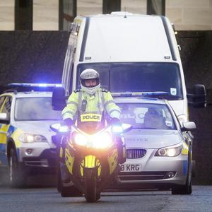 A man arrested in connection with the Stockholm suicide bombing is escorted away from Glasgow Sheriff Court