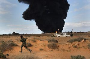 RAS LANUF, LIBYA - MARCH 09:  Libyan rebels advance during a battle with government troops as a facility burns on the frontline on March 9, 2011 near Ras Lanuf, Libya. The rebels pushed back government troops loyal to Libyan leader Muammar Gaddafi towards Ben Jawat.  (Photo by John Moore/Getty Images)