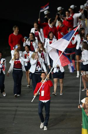 Serbia's Novak Djokovic holds his counties flag at the Opening Ceremony at the Olympic Stadium, London. PRESS ASSOCIATION Photo. Picture date: Friday July 27, 2012. See PA story OLYMPICS Ceremony . Photo credit should read: Mike Egerton/PA Wire. EDITORIAL USE ONLY