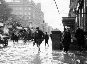 """I found these wonderful photos amongst my late father's possessions.  He was called Bob Ryan and worked in Robinson & Cleavers . The photos  show flooding in Belfast in 1903 in Donegall Square. The note attached  to them was sent by his work colleague Jack Herriot and reads as  follows.  """"Bob, you remember these photos of R&C. Someone gave you or  me them. Floodwater in 1903 taken taken from the same spot probably  using a camera by Rodman who were opposite the Irish Bank at the time.  Note the little straw hat on the girl with the can. Odd that nowadays  in B&H Cafe waitresses wear similar bonnets.""""    Submitted by Kevin Ryan"""