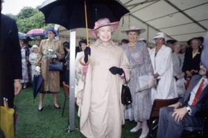The Queen, Elizabeth 11. 1993 visit.The Queen dons a practical cape and a large black umbrella to face the dreadful downpour during the Hillsborough garden party.  June 1993